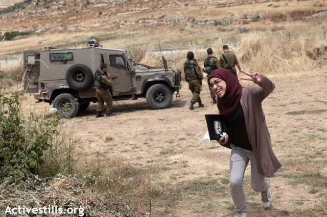 Woman arriving at the spring, passing soldiers (Anne Paq / Activestills)