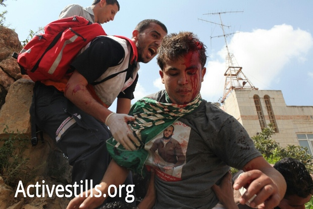 An injured Palestinian receives treatment during the Nakba day protest in support of the Palestinian prisoners, near Ofer Military Prison, May 15, 2012 (photo: Activestills)