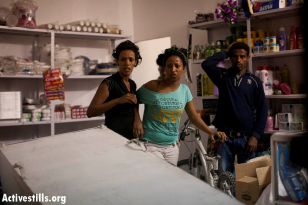 Eritrean refugees react less then a minute after their shop was attacked by a mob following protest against African refugees and asylum seekers in Tel Aviv's Hatikva neighborhood on May 23, 2012.