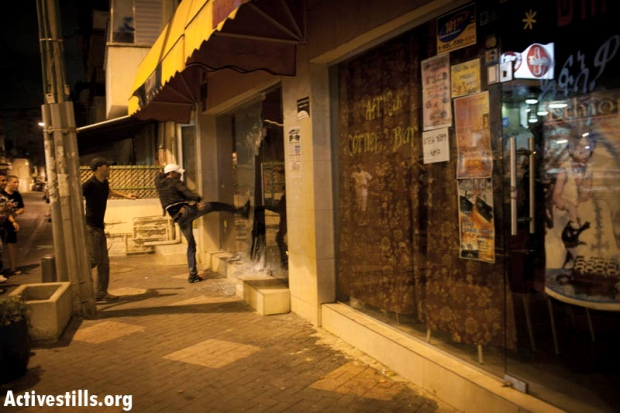 Rioters smashing the window of an Ethiopian bar during a riot in Hatikva neighborhood on May 23, 2012 (photo: activestills)