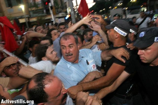 MK Barakeh and police at a Tel Aviv demonstration against 2nd Lebanon War, 2006 (Oren Ziv / Activestills)