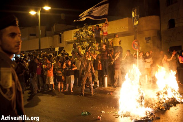 A crowd starting a fire on the main road of Hatikva (Activestills)