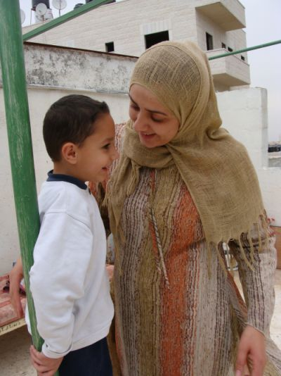 Amira talks with her five-year-old son after he has returned from kindergarten (photo: Mya Guarnieri)