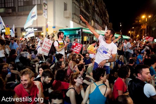 "J14 protesters blocking a Tel Aviv junction. Sign reads ""bring back the welfare state"" (photo: Activestills)"