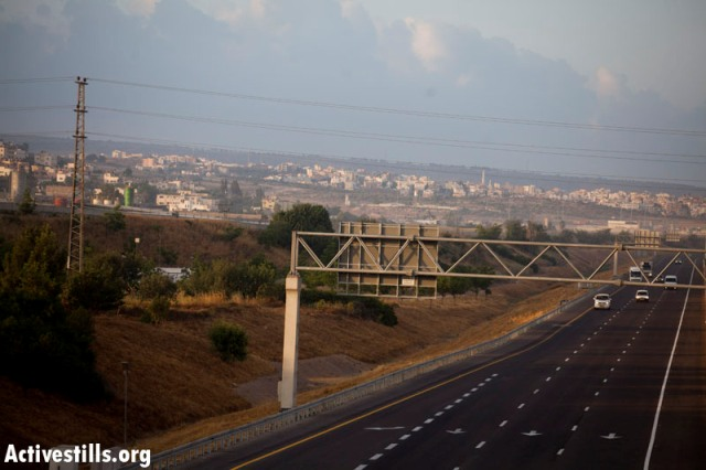 Israel's central toll highway, road 6, and a mount of earth hiding the Tul Karem wall (Oren Ziv / Activestills)