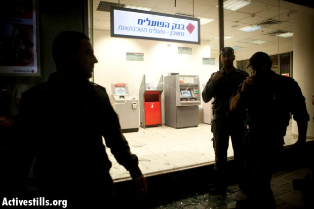 Police officers in front of a bank whose window was smashed during a J14 protest in Tel Aviv, June 23, 2012 (photo: activestills.org)