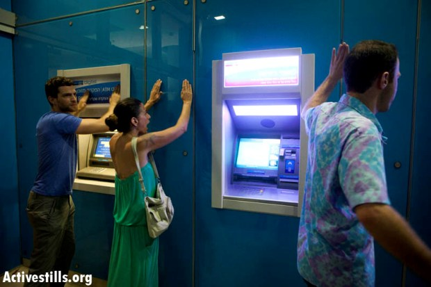 Protesters banging on the wall of a bank during J14 protest in Tel Aviv, June 23, 2012 (photo: activestills.org)