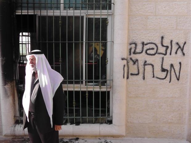 "Pro-settlement graffiti on a torched mosque in Jeba, near Ramallah, reading ""Ulpana, War"" (photo: Iad Hadad/B'Tselem)"