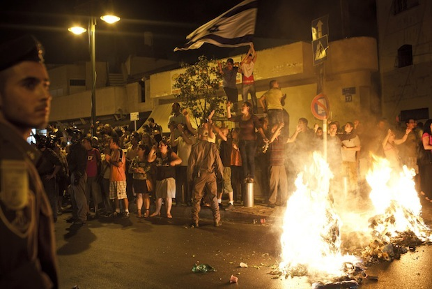 """A mob sets garbage on fire and sings """"The people want the Africans to be burned"""" after a protest against African refugees and asylum seekers in Tel Aviv's Hatikva neighborhood, May 23, 2012. (Activestills.org)"""