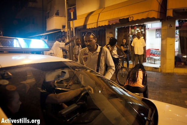 Amin, the owner of an Eritrean bar in south Tel Aviv, speaks to police on Saturday night (photo: Activestills)