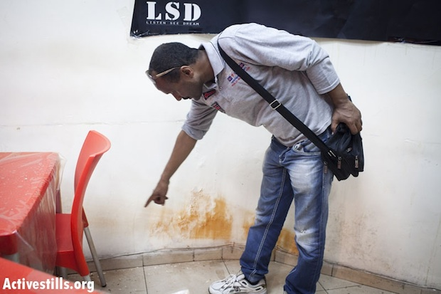 Amin, an owner of an Eritrean bar in south Tel Aviv, points to the marks left by a stun grenade thrown into his bar (photo: Activestills)
