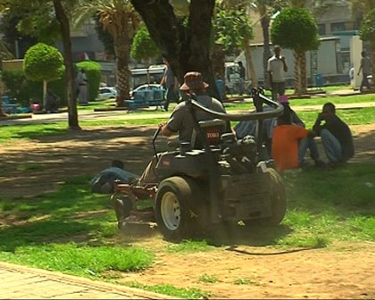 A municipal worker moves the lawn at Lewinsky Park amid loitering Sudanese refugees, including one sleeping on the ground, Tel Aviv, June 11, 2012 (photo: Roee Ruttenberg)