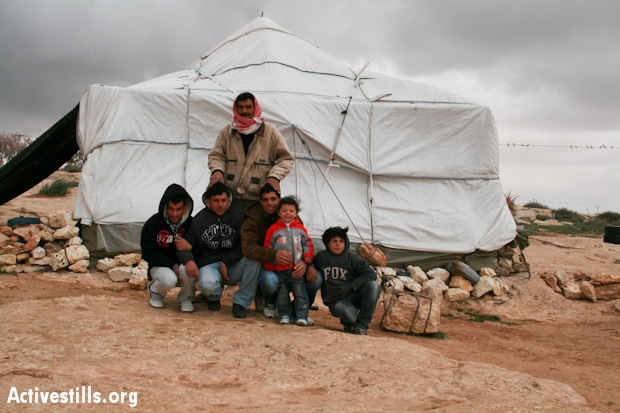 A Palestinian family outside their tent home in the village of Susya, South Hebron Hills. (Photo: Activestills.org)