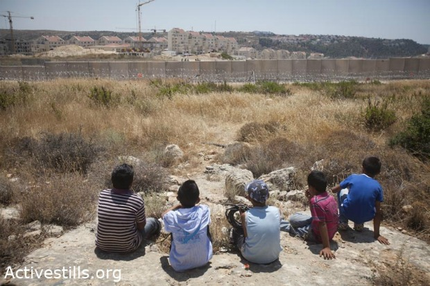 Children of Bil'in sit where the fence once stood, looking at land returned to their village and the new position of the separation wall (photo: activestills.org)