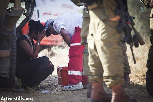 A Palestinian medic treats an injured international activist (photo: Activestills)