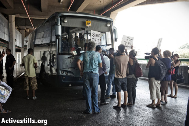 Local activists protest against the deportation and attempt to disrupt the departure of the bus, arguing that conditions in South Sudan are not safe enough for the refugees to be returned there. Tel Aviv, Israel, July 25, 2012. (Photo: JC/Activestills.org)