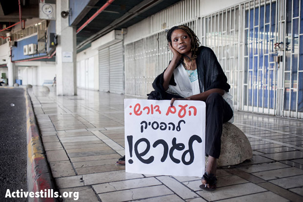 "A woman holds a solidarity sign in Hebrew that reads: ""The people demand to stop the deportations,"" at the seventh deportation to South Sudan. Tel-Aviv, Israel, August 8, 2012. (Photo: Shiraz Grinbaum/Activestills.org)"
