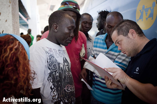 A representative of the Authority of Population and Immigration checks the names of South Sudanese people that are being deported. Tel-Aviv, Israel, August 8, 2012. (Photo: Shiraz Grinbaum/Activestills.org)