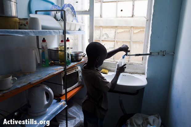 A South Sudanese child in his home fills a bottle of water on the morning of his deportation. Tel Aviv, Israel, June 17, 2012. (Photo: Oren Ziv/Activestills.org)