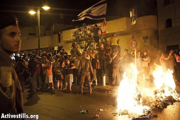 An Israeli mob starts a fire during anti-African asylum seeker riots in Tel Aviv, May 23, 2012 (Activestills)