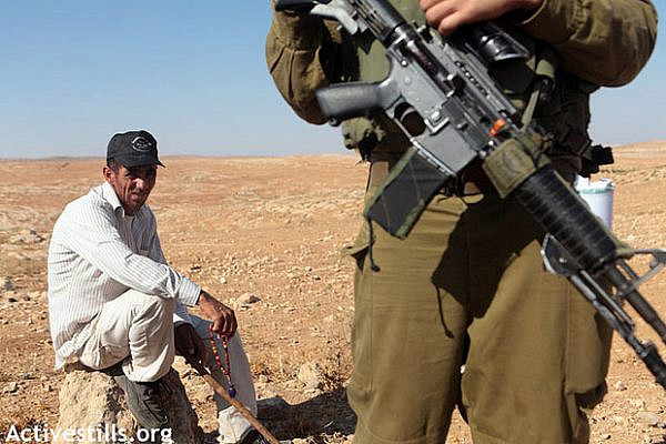 Palestinian shepherd in Um Faqara prevented from reaching his land by IDF soldiers August 2012 (Activestills)