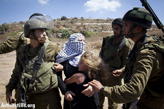 Israel soldiers arresting Nariman Tamimi, an activist from Nabi Saleh,while her 8 year old daughter clings on to her trying to free her, at the entrance to Nabi Saleh's water spring on August 24, 2012, during the violent dispersal of the weekly protest against the occupation held in the village.