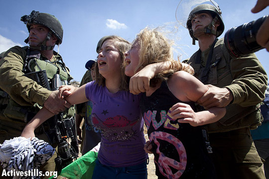 Israel soldiers violently holding onto Nariman Tamimi's daughter and relative as she is being arrested at the entrance to Nabi Saleh's water spring on August 24, 2012, during the violent dispersal of the weekly protest against the occupation held in the village.