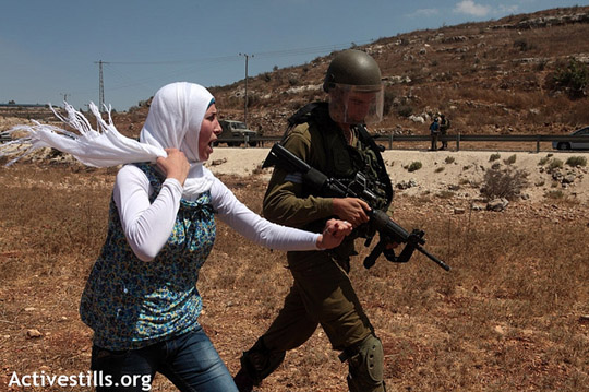 An Israeli soldier prevents a young Palestinian woman from reaching the spring of her village during the weekly protest against the occupation and settlements in the West Bank village of Nabi Saleh, August 24, 2012.