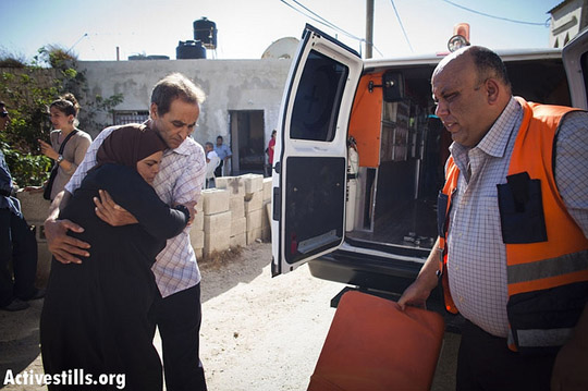 A Palestinian woman being evacuated by an ambulance after Israeli soldiers threw a sound grenade into her living room causing it to explode right by her, during a protest in the West Bank village of Nabi Saleh, August 24, 2012.