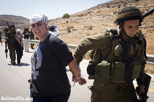 An Israeli solider arrests a Palestinian activist during a protest in the West Bank village of Nabi Saleh, August 24, 2012.