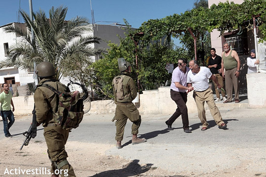 A villager from Nabi Saleh shouts at Israeli soldiers after he was injured during a violent house search conducted by the Israeli army in the center of the village during the weekly protest against the occupation and settlements in the West Bank village of Nabi Saleh, August 24, 2012.