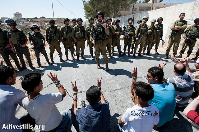 Palestinian activists wrapped in chains in solidarity with prisoners in Israeli jails confront heavily armed Israeli soldiers during a weekly nonviolent demonstration in Al Ma'sara, West Bank, September 14, 2012. The previous day marked 19th anniversary of the Oslo interim peace accords. Calls were renewed for the release of prisoners jailed before the agreement was signed. (photo: Ryan Rodrick Beiler/Activestills.org)