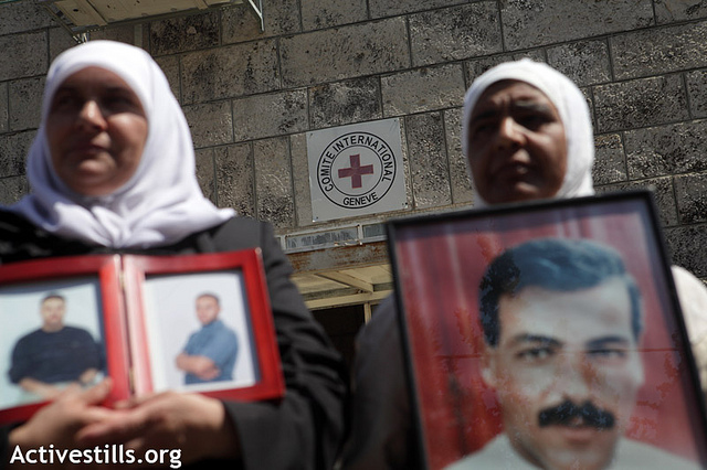 Palestinians hold posters depicting their jailed relatives during a protest for the release of Palestinian prisoners from Israeli jails in front of the office of the International Committee of the Red Cross (ICRC) in the West Bank city of Bethlehem, September 18, 2012. The protest was organized on the same day that Palestinian prisoners launched a one-day hunger strike in solidarity with four prisoners currently undertaking a prolonged strike action. On that day, Samer al-Barq was on his 120th day of renewed hunger strike, Hassan Safadi was on renewed hunger strike for 90 days, and Ayman Sharawna had refused food for 80 days. (photo: Anne Paq/Activestills.org)