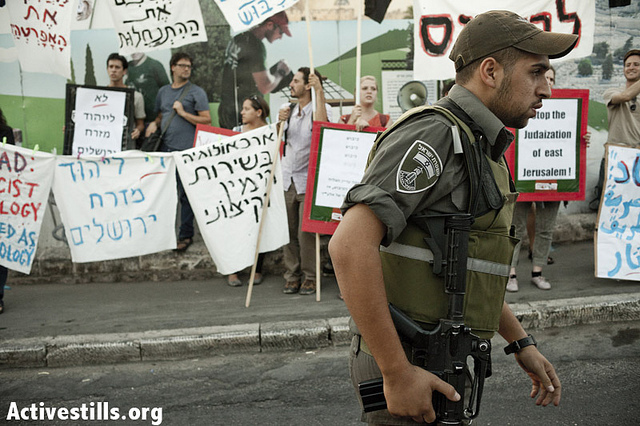 Israeli activists hold a protest against the Judaization of East Jerusalem in front of the City of David settlement in Silwan, East Jerusalem, on September 6, 2012. The protest took place as 'Elad', which is responsible for the settlement, held its 13th annual archaeological conference, showcasing its achievements in excavating Silwan and restoring the neighborhood's supposed Jewish heritage. Alongside its extensive archeological and tourist activities, Elad also established several residential settlements in Silwan, founding a Jewish presence in the heart of a Palestinian neighborhood, and setting in motion a chain of events which last year resulted in a series of clashes with hundreds of arrests and at least two deaths. (photo: JC/Activestills.org)