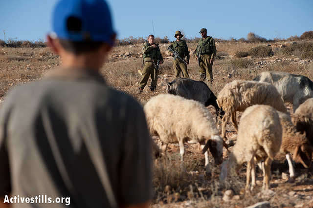 A Palestinian shepherd boy faces Israeli soldiers while grazing his flock on land near his village of Mufaqara, September 18, 2012. The soldiers guard the Israeli settlement outpost of Avigail and routinely deny Palestinians' legal right to graze on adjacent land. While all Israeli settlements in the West Bank are considered illegal under international law, such outposts are considered illegal even under Israeli law. (photo: Ryan Rodrick Beiler/Activestills.org)