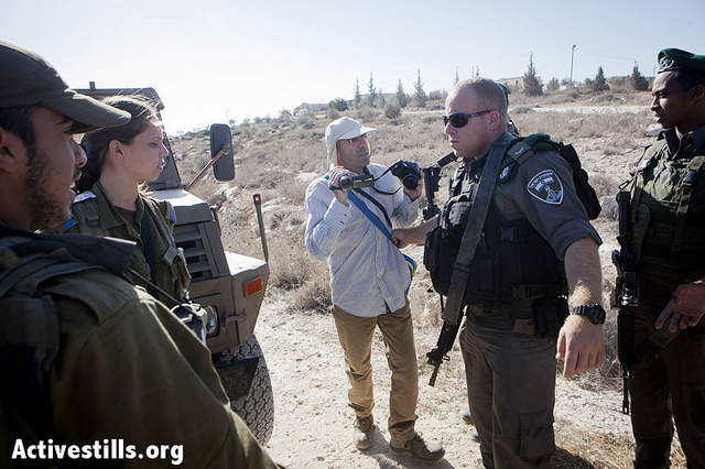 An Israeli activist being asked to leave the place of the attack and stop filming by an officer of the Israeli army forces, seen on September 18, 2012. (photo: SG/Activestills.org)