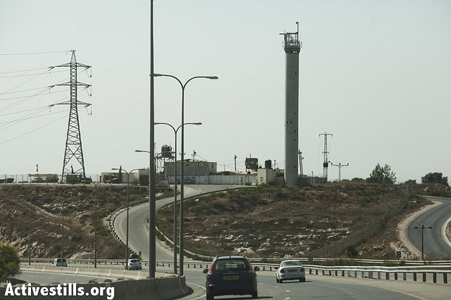 An Israeli army watchtower seen from road 443 in the West Bank, on September 16, 2012. Road 443, built on occupied territory and largely inaccessible to Palestinian cars without an Israeli license plate (which is the case for all cars owned by Palestinians residing in the occupied territories), connects Jerusalem to the center of Israel and effectively cuts off a section of the West Bank from the rest of the Palestinian territories. With thousands of Israelis taking advantage every day of this shorter route from Tel Aviv to Jerusalem and seeing no problem with using a segregated road often flanked on both sides by a concrete wall, Road 443 is a telling symbol of how normalized the occupation has become in Israeli society. (photo: JC/Activestills.org)
