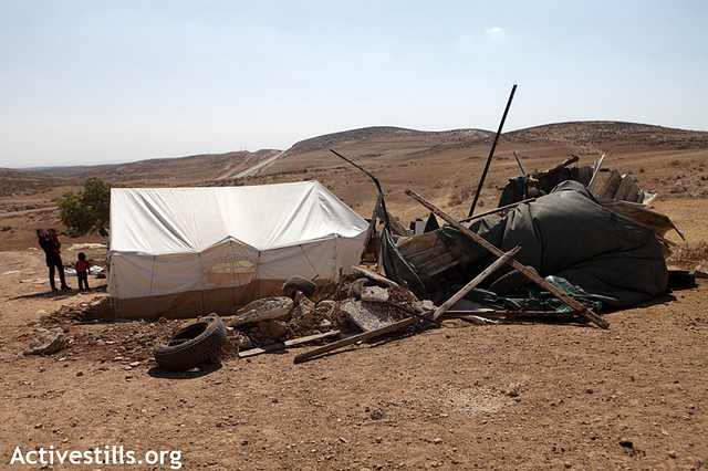 A tent provided by the Red Crescent stands next to what remains of a residential structure that was demolished earlier by the Israeli army in Khirbet Zanuta, South Hebron Hills, August 28, 2012.(photo: Anne Paq/Activestills.org)