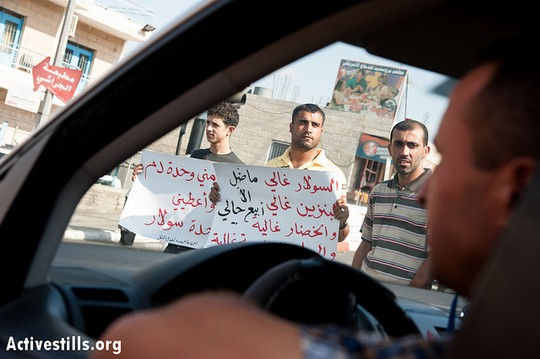 """A Palestinian motorist is confronted by taxi and truck drivers blocking traffic at Bethlehem's Bab Iskak intersection to protest the high cost of fuel and food, September 10, 2012. The sign on the left reads, in effect, """"Take my blood, and give me the same amount of diesel."""" (photo by: Ryan Rodrick Beiler/Activestills.org)"""