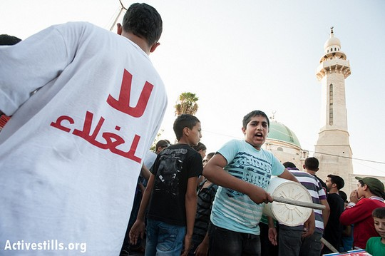 """A Palestinian youth wears at T-shirt saying """"No to High Prices"""" while another beats a plastic bucket in a march in the West Bank city of Bethlehem, September 10, 2012. (photo: Ryan Rodrick Beiler/Activestills.org)"""