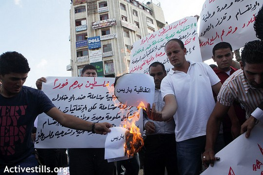 """Palestinians burn papers reading """"Paris Agreement"""" during protests in Ramallah, September 11, 2012. (photo: Anne Paq/Activestills.org)"""