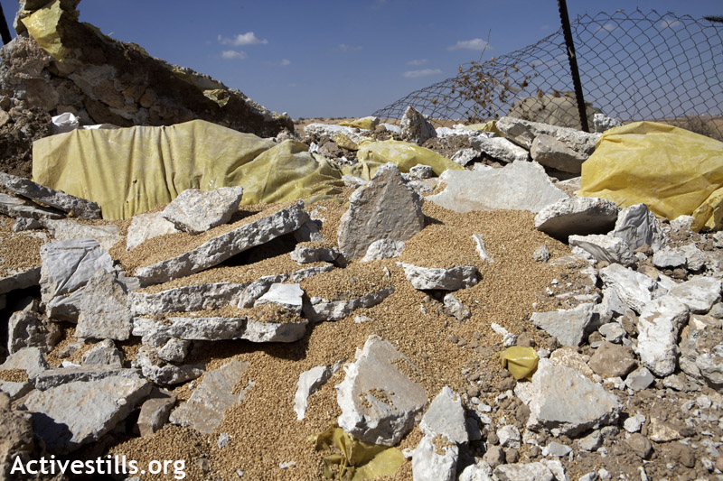 Spoiled wheat after the concrete block in which it was stored was demolished during a wave of demolitions in Khirbet Zanuta, South Hebron Hills, August 28, 2012. (photo: Anne Paq/Activestills.org)