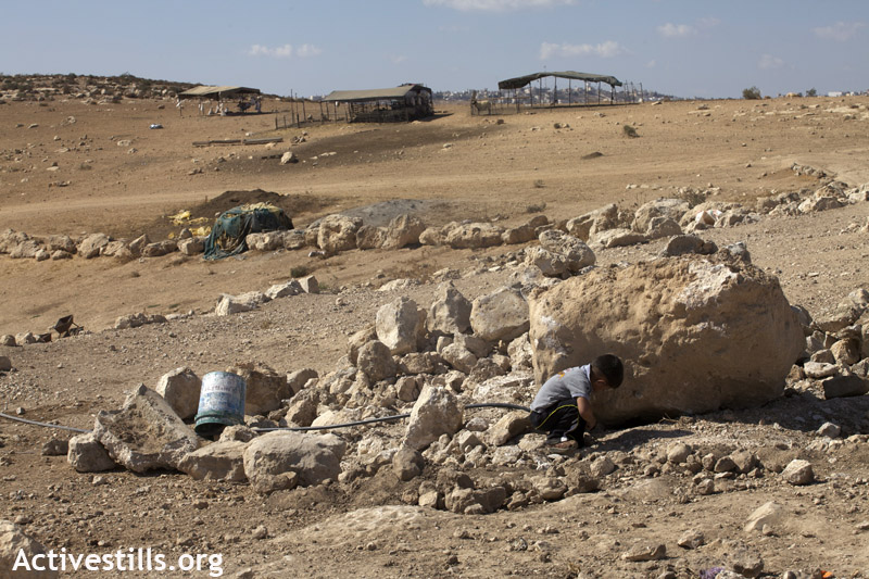 A Palestinian child of Khirbet Zanuta crouches near a well demolished earlier in the day by the Israeli army.(photo: Anne Paq/Activestills.org)