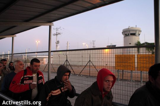 Palestinian workers line up at a checkpoint to enter Israel. (photo: flickr/Anne Paq, Activestills)