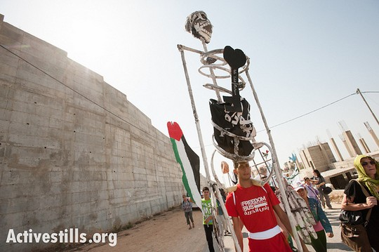 Carrying giant puppets, Palestinians of Al-Walaja, together with Palestinian, international, and Israeli supporters organized by the Freedom Bus campaign march through the West Bank village of Al-Walaja to protest the Israeli separation wall, September 28, 2012. (photo: Ryan Rodrick Beiler/Activestills.org)