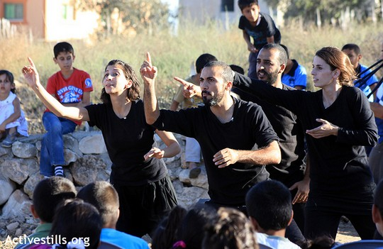 The Freedom Bus ensemble performs in solidarity with Faq'ua village near the West Bank city of Jenin, September 23, 2012. The people of Faq'ua shared personal stories about daily life under Israeli occupation. The Freedom Bus ensemble turned each story into a piece of improvised theater. (photo: Ahmad Al-Bazz/ Activestills.org)