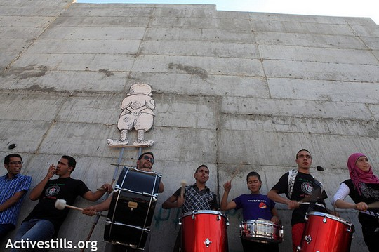 In the shadow of the Israeli separation wall, youth from Al Walaja play drums under a Handala figure, a symbol of Palestinian refugee rights, during a march and cultural event as part of the Freedom Bus tour in the village of Al Walaja, September 28, 2012. (photo: Anne Paq/Activestills.org)