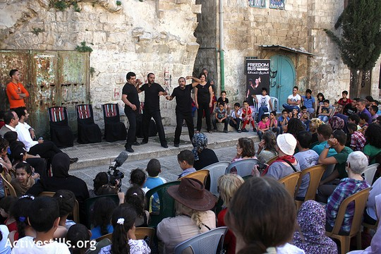 The Freedom Bus ensemble performs in the old city of Nablus, September 24, 2012. Local residents shared personal stories about life under Israeli occupation and the Israeli invasion of 2002. The Freedom Bus ensemble turned each story into a piece of improvised theater. (photo: Ahmad Al-Bazz/ Activestills.org)