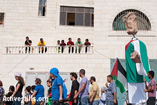 Carrying giant puppets, Palestinian, international, and Israeli supporters march through the West Bank village of Al Walaja during a Freedom Bus event, September 28, 2012. (photo by: Ryan Rodrick Beiler/Activestills.org)