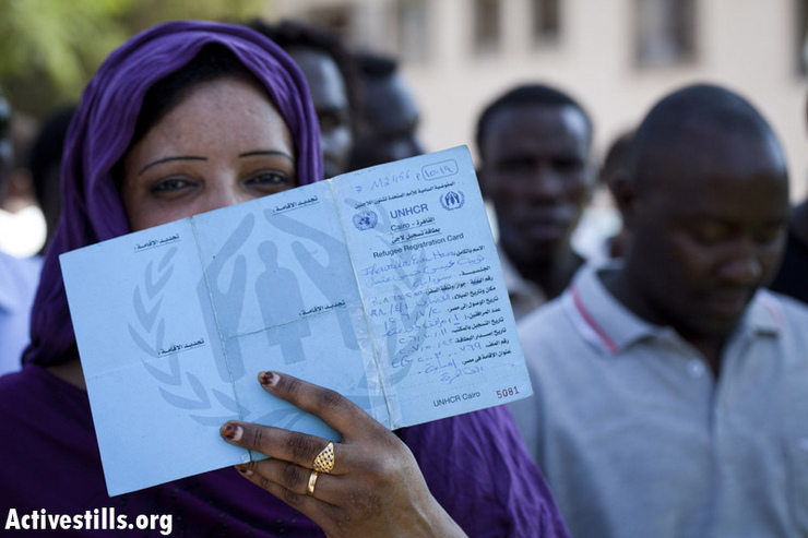 A Sudanese woman shows her UNHCR Refugee card from Egypt as Sudanese refugees protest in front of the government's offices in center Tel Aviv against the plan to imprison refugees, October 14, 2012. Israel is building a new facility that could house thousands of additional asylum seekers in the Negev Desert. (photo by: Oren Ziv/ Activestills.org)